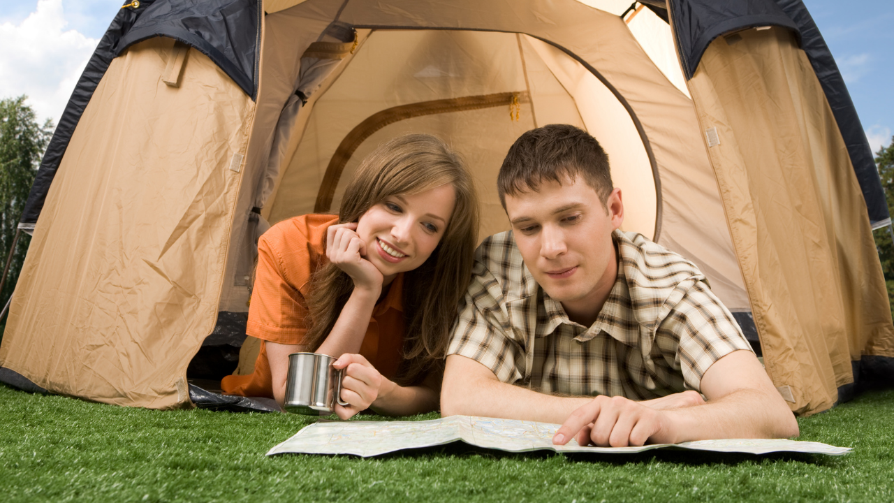 Young couple lying near their tent looking at a map.