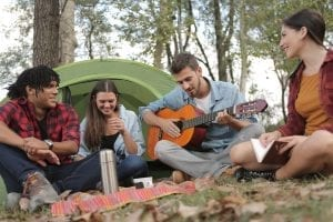 Image: Young adults on ground in front of a tent with a guitar